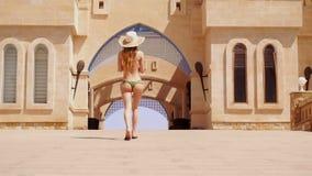 En ung flicka i en baddräkt och en hatt med sexiga bakdelar går i ultrarapid stock video