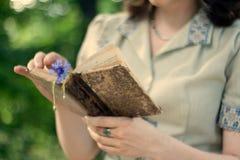 En ung flicka i en bok för tappningklänninginnehav Royaltyfri Bild