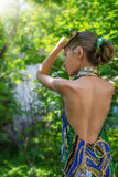 En ung flicka i en klänning med nakenstudie drar tillbaka värde i lövverket i trähåret som dekoreras med lövverk Royaltyfri Foto