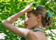 En ung flicka i en klänning med nakenstudie drar tillbaka värde i lövverket i trähåret som dekoreras med lövverk Royaltyfri Fotografi