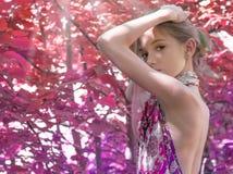 En ung flicka i en klänning med nakenstudie drar tillbaka värde i lövverket i träna, rött skoghår som dekoreras med lövverk Arkivfoto