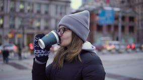 En ung flicka i ett svart omslag och hatt går runt om den härliga Shanghaien med kaffe i hennes händer stock video