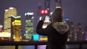 En ung flicka i ett svart omslag och hatt tar bilder av Shanghais dragningar på mobiltelefonen lager videofilmer