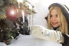 En ung flicka i ett svart omslag trycker på istappar Royaltyfria Bilder