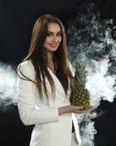 En ung flicka i ett vitt omslag rymmer en ananas i henne händer och leenden på en svart bakgrund som täckas med rökdunsten Arkivbilder