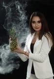 En ung flicka i ett vitt omslag rymmer en ananas i henne händer och leenden på en svart bakgrund som täckas med rökdunsten arkivfoto