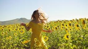 En ung flicka i en gul klänning kör i solrosor långsam rörelse arkivfilmer