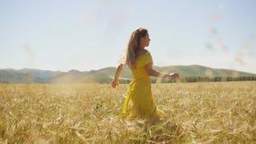 En ung flicka i en gul klänning med lång hårspring på ett vetefält långsam rörelse arkivfilmer