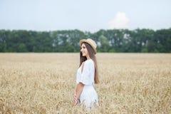 En ung flicka i en hatt är en båtuthyrare som tycker om naturen av ett vetefält Härlig flicka i vita klänningkörningar på fältet  royaltyfri foto