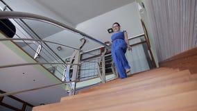 En ung flicka i hennes hus går på en härlig trätrappuppgång lager videofilmer