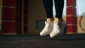 En ung flicka i idrottshallen är det hoppa repet stock video