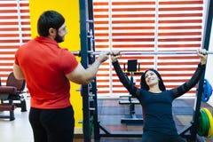 En ung flicka i idrottshallen som gör med en personlig instruktör royaltyfri foto