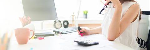 En ung flicka i kontoret rymmer en rosa markör, exponeringsglas och arbete med dokumentationen arkivfoton