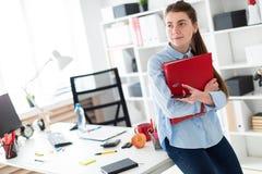 En ung flicka i kontoret står och att luta på en tabell och rymmer en telefon och en mapp med dokument Arkivfoto