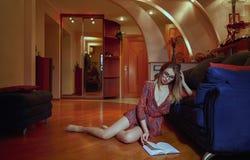En ung flicka i en kort klänning hemma som läser en bok som lutar på soffan royaltyfri fotografi