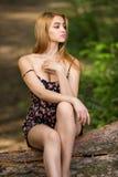 En ung flicka i en kort klänning sitter på en inloggning en sommarskog royaltyfri foto