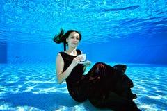 En ung flicka i en purpurfärgad klänning sitter undervattens- längst ner av pölen och att rymma en vit kopp i hennes hand som ser arkivbilder