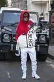 En ung flicka i en röd hoodie, exponeringsglas och ett vitt isberg för firma för sportomslag poserar framme av en Mercedes som po Royaltyfri Foto