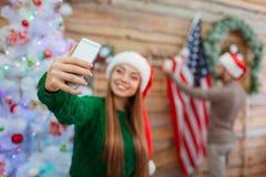En ung flicka i en santa hatt gör en selfie på bakgrunden av en man som hänger en amerikanska flaggan på väggen royaltyfri bild