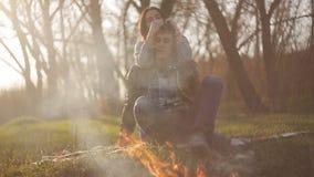 En ung flicka kramar hennes pojkvän på ett datum vid branden Grabben och flickan beundrar flamman av branden arkivfilmer