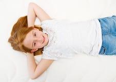 En ung flicka ligger på sängen Kvalitets- madrass royaltyfri foto