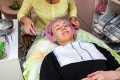 En ung flicka ligger på soffan med en rosa hatt på hennes hår, medan utföra en darsonvalization på framsida med en special appara arkivfoto