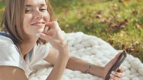 En ung flicka ligger på en vit pläd i parkera och ringer ett meddelande på telefonen stock video