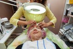 En ung flicka ligger p? en soffa under kosmetiska tillv?gag?ngss?tt med en maskering p? framsidan som kosmetologkvinnan pressar o royaltyfria foton