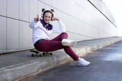 En ung flicka lyssnar till musik och sjunger på en skateboard royaltyfria bilder