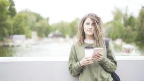 En ung flicka lyssnar till en musik som dricker utomhus en kopp kaffe Fotografering för Bildbyråer