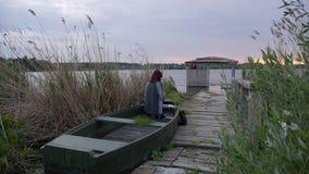 En ung flicka målar i ett fartyg på solnedgången arkivfilmer