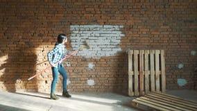 En ung flicka målar en tegelstenvägg i hennes hus med en rulle Målningväggar med en rulle Måla de kala väggarna med a lager videofilmer