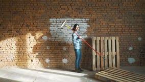 En ung flicka målar en tegelstenvägg i hennes hus med en rulle Målningväggar med en rulle Måla de kala väggarna med a arkivfilmer