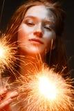 En ung flicka med bengal ljus och rött hår En härlig modell med glänsande hud och blänker smink ` S för nytt år och en ferie im arkivbild