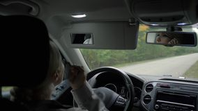 En ung flicka med blont hår målar henne ögon, medan sitta i en bil lager videofilmer