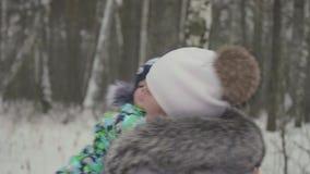 En ung flicka med ett barn som spelar i vinter, parkerar Går i den nya luften arkivfilmer