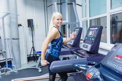 En ung flicka med ett leende som kör på trampkvarnen i idrottshallen fotografering för bildbyråer