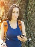 En ung flicka med ett ryggsäckbruk telefonen royaltyfri foto