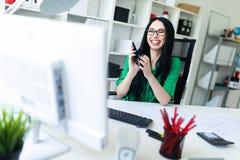 En ung flicka med exponeringsglas i kontoret rymmer en telefon i henne händer och att skratta Arkivfoto