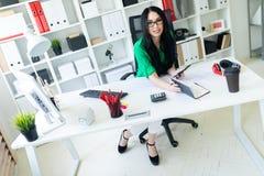 En ung flicka med exponeringsglas i kontoret sitter på tabellen och rymmer en dagbok och en telefon i henne händer Royaltyfri Bild