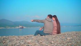 En ung flicka med en grabb som på våren sitter och talar på stranden Flickan och grabben i ramsnurrandena lager videofilmer