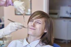 En ung flicka med en kort frisyr sitter i stolen för tandläkare` s Ansiktsuttryck med fasa och skräck av smärtar från tandläkare royaltyfri bild