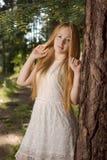 En ung flicka med långt blont hår som står i skogen Arkivfoto