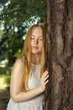 En ung flicka med långt blont hår som står i skogen Arkivfoton
