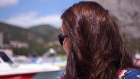 En ung flicka med långt hår som vinkar hennes hand som passerar ett fartyg med turister HD 1920x1080 långsam rörelse arkivfilmer