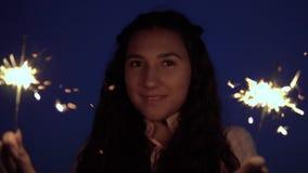 En ung flicka med långt mörkt hår står med fyrverkerier i hennes händer mot bakgrunden av nattstaden långsam rörelse lager videofilmer