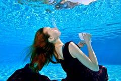 En ung flicka med rött hår i en härlig klänning är att simma som är undervattens- i pölen på en blå bakgrund royaltyfria foton