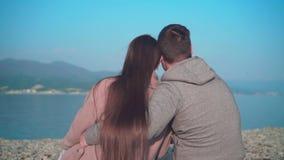 En ung flicka med sittande krama för grabb på stranden på våren Flickan och grabben i ramsnurrandena stock video