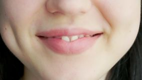 En ung flicka med stora kantskratt och leenden lager videofilmer