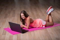 En ung flicka med en svart bärbar dator som ligger på en träbakgrund En sportive flicka i en färgrik sportswear Sportbegrepp Arkivbilder